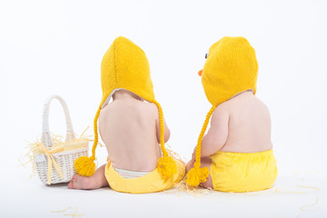 Two babies in chicken costumes with white basket from behind