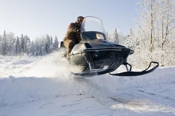 snowmobile driving through a harsh winter landscape