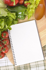 Salad with blank recipe book and chopping board