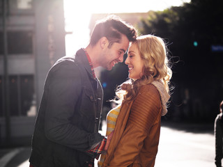 couple on street in city flirting with lens flare