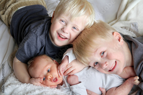 Big Brothers Hugging Newborn Baby Sister - 80359842