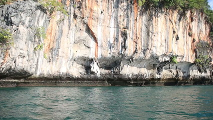 colourful cliffs hang over azure sea in thailand