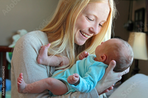 Young Mother Smiling at Newborn Baby in Home Nursery - 80360422