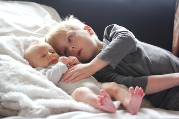 Big Brother Lovingly Playing with Newborn Baby Sister
