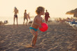 Summer vacation - little girl playing on sandy beach at sunset