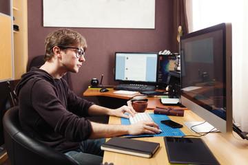 Freelance developer and designer working at home, man using desk