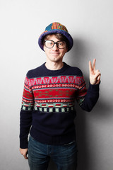 Young handsome man in knit colourful clothes, gray wall behind