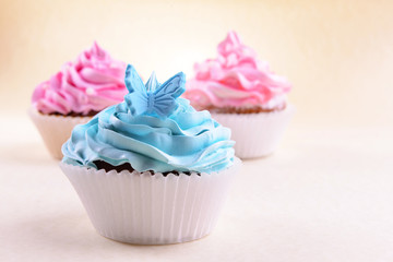 Delicious cupcakes on beige background