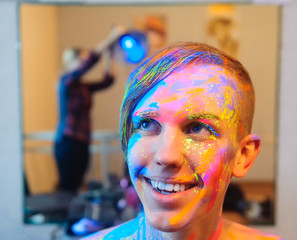 Young man preparing for photo with bodyart painting
