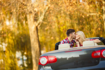 Loving couple in a black convertible in the autumn park.