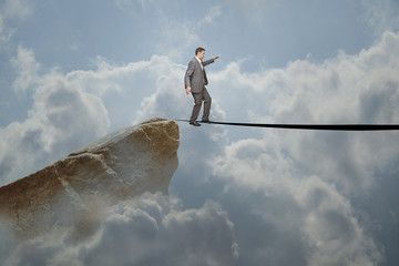 Man in balance on a line in the clouds