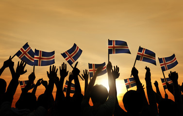 Group of People Waving Icelandic Flags in Back Lit