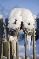 old shoes hanging on a fence in winter in a russian village