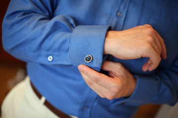 Man in business attire adjusts his cuff links