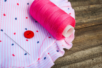 Pink threads, buttons and needles on fabric