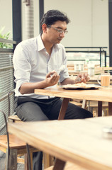 Asian Indian business man reading newspaper while drinking a cup