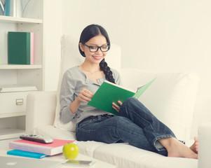 asian girl reading book in living room