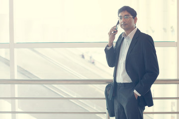 Closeup of confident young businessman using cell phone in hotel