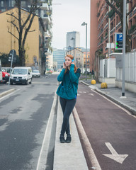 Beautiful girl listening to music in the city streets