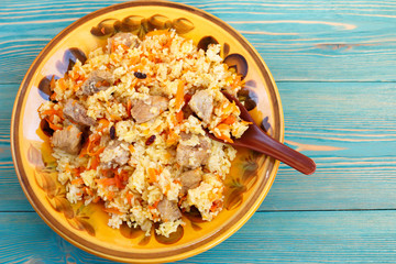 traditional oriental pilaf, rice with meat and carrot on blue