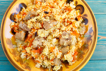 oriental pilaf, rice with meat and carrot on yellow plate