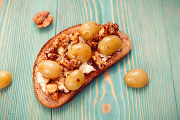 rye toast with ricotta, grape and walnut on blue table