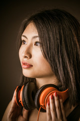 Young Asian beauty with stereo headphones