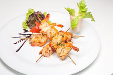Skewered jumbo shrimps with sauce