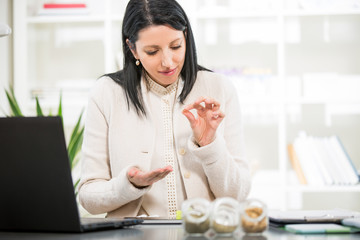 Businesswoman takes homeopathic pills