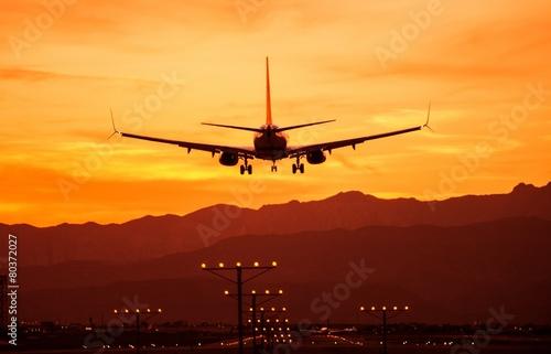 Leinwanddruck Bild Landing Airplane at Sunset
