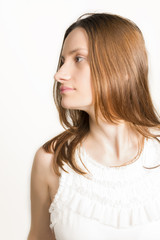 Profile of sad beautiful woman in white dress, studio shot