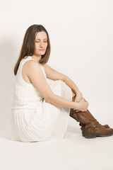 Sad beautiful woman in white dress and brown boots