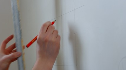 Builder draws marking on the wall. Worker making measurements.