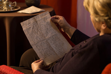Senior woman reading yellowed letter