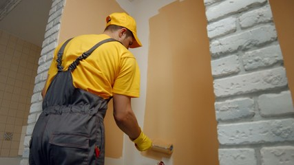 House painter paints the wall in brown.