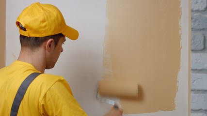 Builder paints white wall in beige color with a roller.