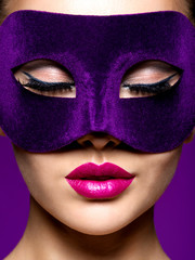 Woman in purple theatre mask on face with violet lips