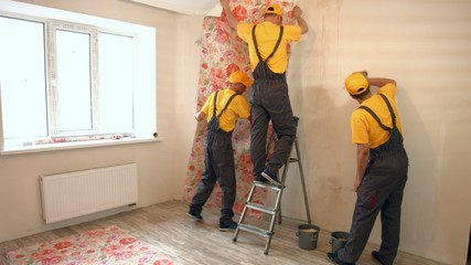 Specialists wallpapering in the house.