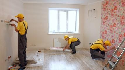 Team of builders make repairs living room.