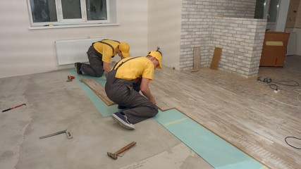Team of builders make renovation of apartment. Laying parquet.