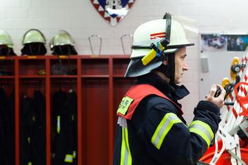 Feuerwehrmann in der Wache mit Funkgeraet
