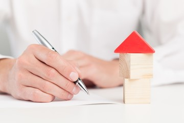 Home. Conceptual image of a man signing a mortgage or insurance