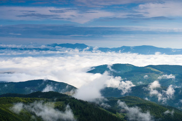 Clouds in the morning rise over the mountains in the Carpathians