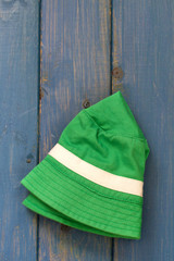 green baby hat on blue background