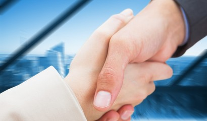 Composite image of close up on new partners shaking hands