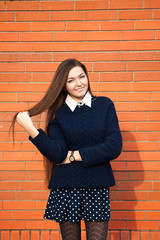 Young woman straightens her hair on a red wall