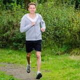 Fototapeta junger mann joggt durch einen park