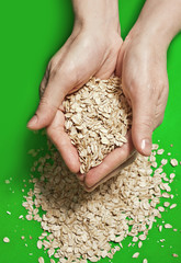 Hands holding oats on the green background