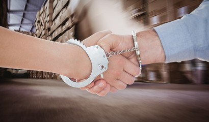 Composite image of handcuffed business people shaking hands