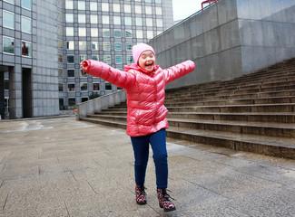 Portrait of beautiful happy little girl in the city